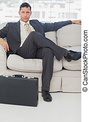Businessman sitting with legs crossed on the couch - Serious...