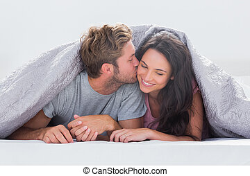 Attractive man kissing his wife under the duvet in bed