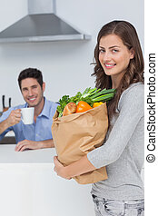 Attractive woman holding groceries bag while her husband is...