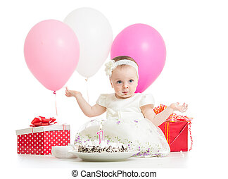 Joyful baby girl with cake, balloons and gifts. Isolated on white.