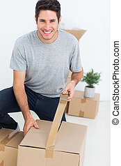 Cheerful man wrapping a box while he is moving home
