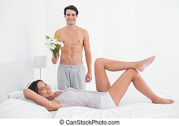 Shirtless man offering a bunch of flowers to his girlfriend...