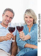 Couple toasting to the camera with red wine on the couch at...