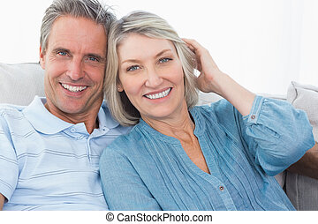 Smiling couple on their couch looking at camera