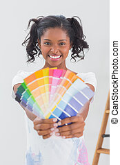 Excited woman showing colour charts against a blank wall