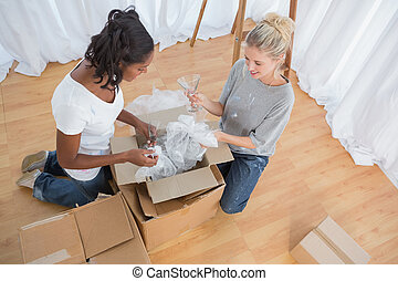 Young housemates unpacking boxes in new home and chatting...