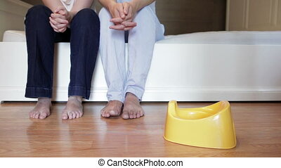 How to teach kid to use potty - Young parents are sitting on...