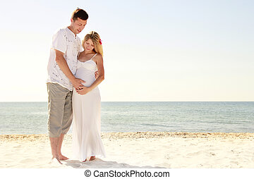 Pregnant couple in love on the beach - a Pregnant couple in...