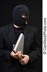 Stealing Office Equipment - A business thief wearing a black...