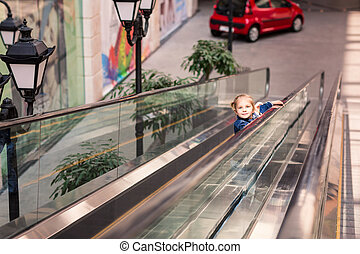 Cute little child in shopping center on escalator