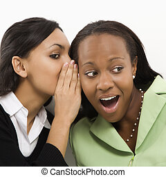 Women gossiping - Indian young adult woman whispering in ear...