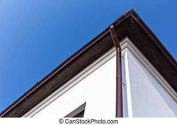 Eavestrough with gutter system - Corner of house with...
