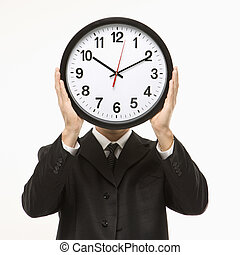 Clock in front of face.