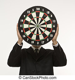 Dartboard in front of face. - Caucasian man wearing suit and...