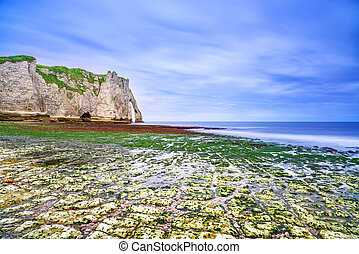 Etretat Aval cliff landmark and its beach in low tide under...