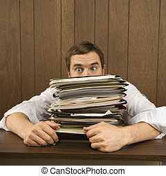 Man with heavy workload. - Mid-adult Caucasian male peeking...