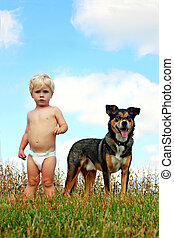 Little Boy and His Dog - a cute little blonde baby boy is...