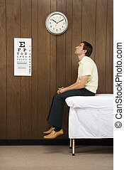 Patient in medical room. - Caucasian mid-adult male waiting...