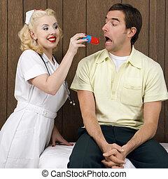 Nurse giving patient pill.