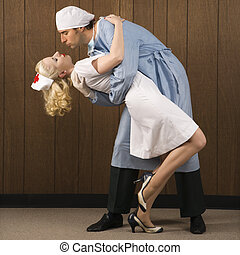 Doctor and nurse romance. - Mid-adult Caucasian male surgeon...