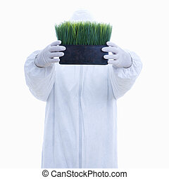 Biohazard man with grass - Man in biohazard suit holding pot...