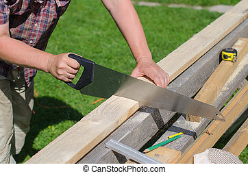 Handyman sawing long wooden plank outdoors