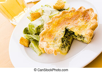 Quiche - Individual spinach quiche served with salad.