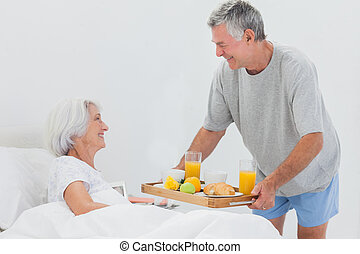 Mature man bringing wife breakfast in bed with orange juice...