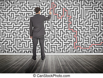 Businessman tracing a red line on a maze drew on the wall