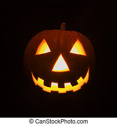 Lit up pumpkin. - Carved Halloween pumpkin glowing in the...