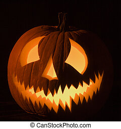 Glowing jack-o-lantern. - Carved Halloween pumpkin glowing...
