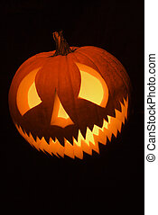 Lit jack-o-lantern. - Carved Halloween pumpkin glowing in...