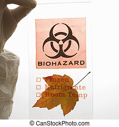 Leaf in biohazard bag - Hand wearing white rubber glove...