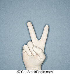 Hand giving peace sign. - Hand wearing white rubber glove...