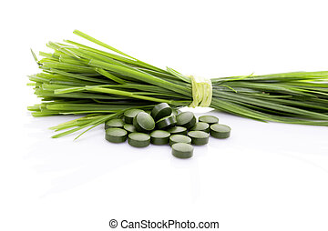 Superfood. - Wheatgrass blades and green pills isolated on...