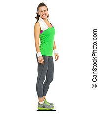 Smiling fitness young woman standing on scales