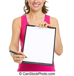 Closeup on fitness trainer giving clipboard for sign