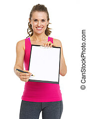 Smiling fitness trainer giving clipboard for sign