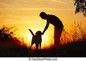Man with dog - Young man with his yellow labrador retriever...