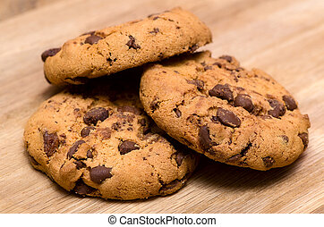 Chocolate chip cookies on a wooden boards background.