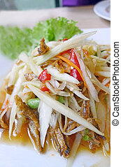 Thai papaya salad (Som Tum) on white plate