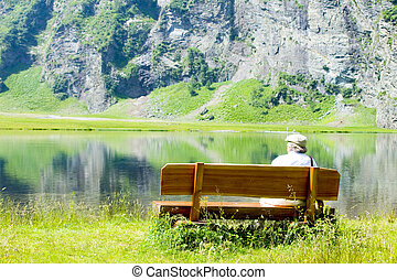 old man sitting on a wooden bench near a lake