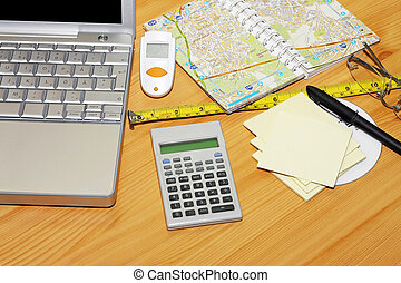 Travel map - Notebook map and calculator at wooden desk
