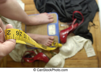 weight worries - young woman on scale with tape measure in...