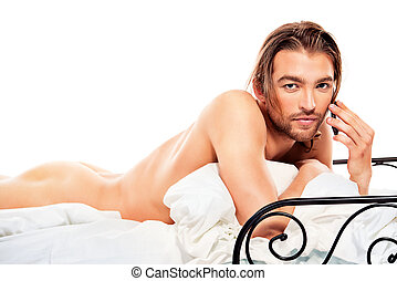 bedroom - Handsome nude man lying in a bed and talking on...