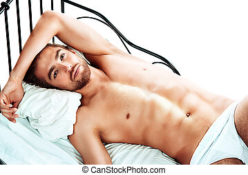 skivvies ad - Handsome nude man lying in a bed. Isolated...