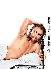 Handsome nude man lying in a bed Isolated over white