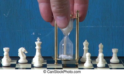 sandglass on chessboard and chess