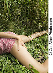Woman in grass. - Young Caucasian woman lying in grass with...