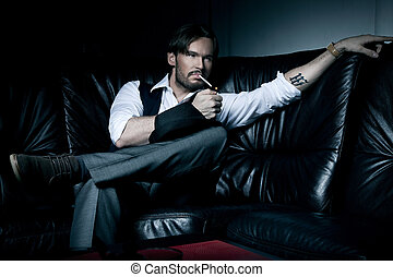 Sexy brunette man on the black couch smoking a cigarette